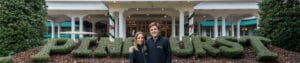 Image of man and woman standing in front Pinehurst Hotel